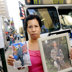 Gertrude Taylor holds photos of her brother Alvin Taylor, who is currently on tour of duty in Afghanistan and is facing losing his job as an MTA bus driver.